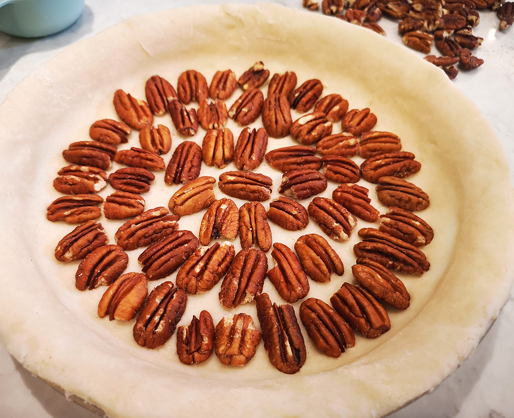 Putting a layer of pecans in the bottom